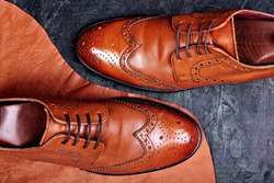 Fashion classical polished men's brown oxford brogues on piece of leather dark wooden background.Top view.