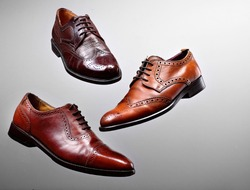 Fashion classical polished men's brown oxford brogues shades of brown oxford brogues.Conept flying shoes.Gray background.Copy space
