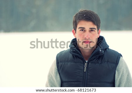 Fashion close up portrait of a handsome young man enjoying himself in winter