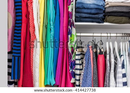 Fashion clothes in walk-in clothing closet or store display for shopping display. Colorful choices of trendy outfits well arranged in clean racks. Spring cleaning concept. Summer home living wardrobe.