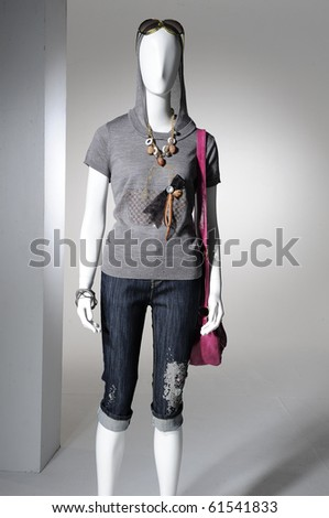 Fashion clothes on a mannequin holding bag - stock photo