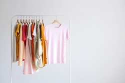 fashion clothes on a stand in a light background indoors. place for text