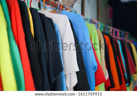 Fashion clothes on clothing rack - bright colorful closet. Close-up of rainbow color choice of trendy female wear on hangers in store closet or spring cleaning concept. Summer home wardrobe.