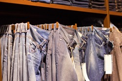 Fashion clothes on the shelves in the store. Jeans, shirts, pants hanging on hangers in the fashion store. Storefront, sale, shopping