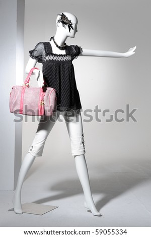 Fashion clothing on mannequin holding bag