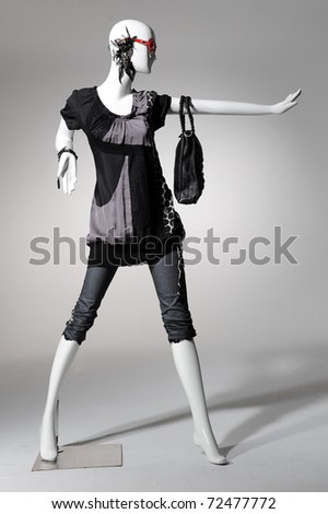 Fashion clothing on mannequin holding bag posing