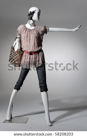 Fashion clothing on mannequin with bag on light background