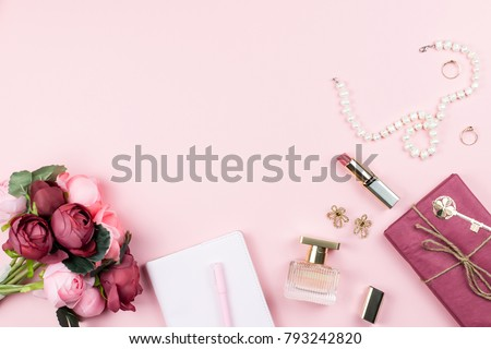 Fashion collection with accessories, flowers, cosmetics and jewelry on pink background, copyspace. Womens Day concept