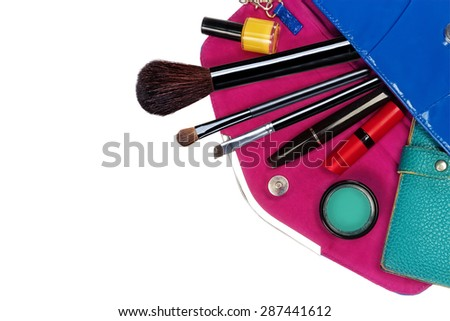 Fashion concept. Colorful make up items and wallet on top of the woman purse.