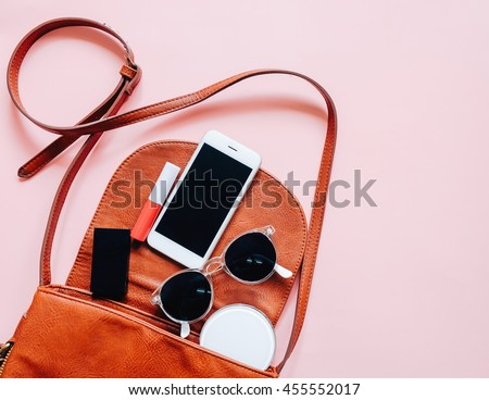 Fashion concept : Flat lay of brown leather woman bag open out with cosmetics, accessories and smartphone on pink background