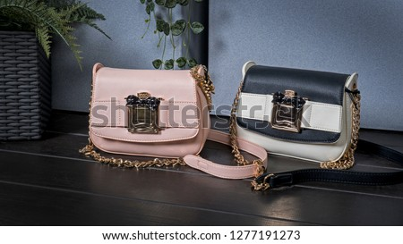 Fashion Concept. Pink and beige with black ladies handbags  quite classy and elegant look a must for women's wardrobe, beautifully designed with the golden chain.  A Wooden Background. #1277191273