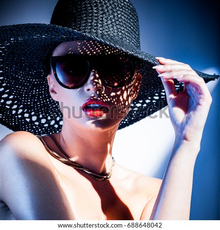 fashion concept - portrait of a beautiful woman in big hat and sunglasses in mixed contrast light #688648042