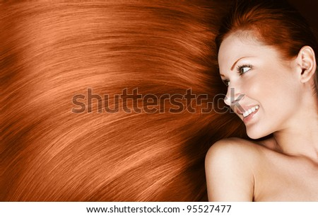 fashion concept portrait of a woman with beautiful long red healthy shiny hair