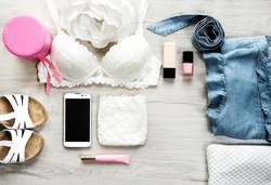 Fashion concept.Still life of fashion woman.Top view of female fashion accessories for woman.Women's Accessories:White lace underwear, wallet, mobile phone, jeans, nail polish, lip gloss,white sandals