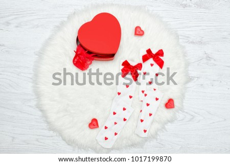 Fashion concept. White stockings and box in the shape of heart. White fur #1017199870