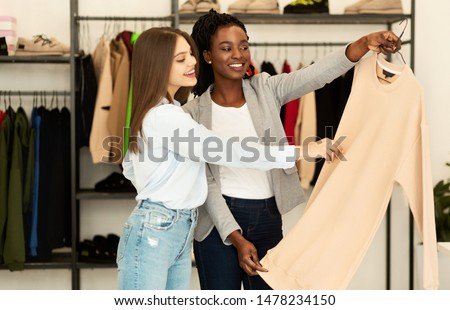 Fashion Consultant. Personal Stylist Choosing Fashionable Designer Clothing For Her Client In Showroom.