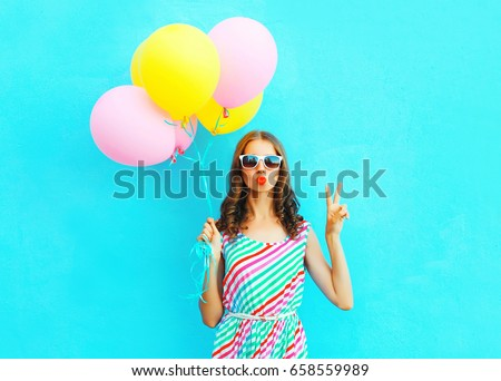 Fashion cool girl blowing lips making kiss an air colorful balloons on a blue background #658559989