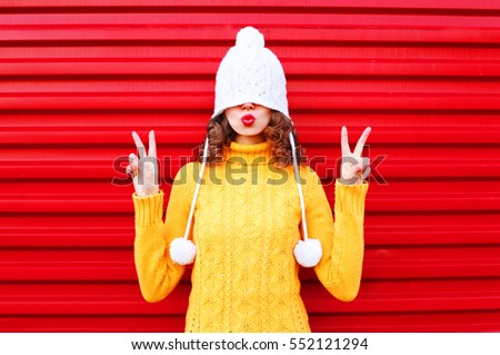 Fashion cool girl blowing red lips makes air kiss wearing colorful knitted hat, yellow sweater over red background #552121294