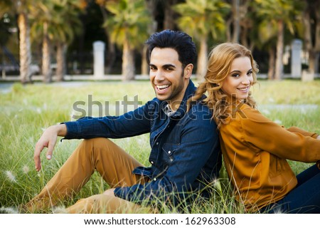 Fashion couple sitting in a grass field back to back