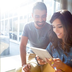 Fashion couple using a tablet with sunbeams and lens flare