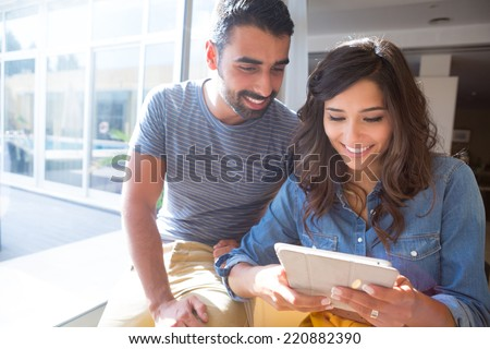 Fashion couple using a tablet with sunbeams and lens flare #220882390