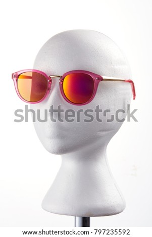 Fashion design glasses wearing on a white mannequin against white background.