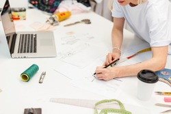 Fashion designer draws a sketch in the studio.  creative workplace for clothing production.