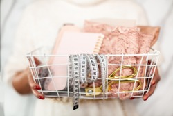 Fashion designer hands holding folded lace fabric, tailoring scissors, measuring tape and notepads in white mesh basket. Tailor tools for measurement and sewing evening dress from lace fabric.