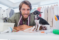 Fashion designer looking at camera with his chihuahua sitting on desk