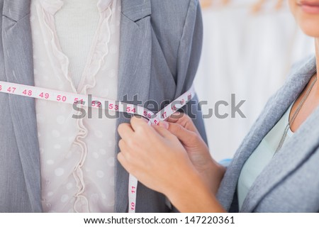 Fashion designer measuring blazer with measuring tape #147220361