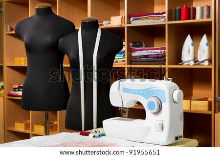 Fashion designer studio with dressmakers professional equipment: mannequin, cloth, sewing machine, irons, Patterns of clothing
