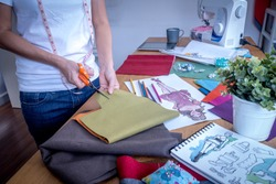Fashion designer (tailoress) cutting fabric while working with drawing sketch, sewing machine, material  at worktable / Garment business concept