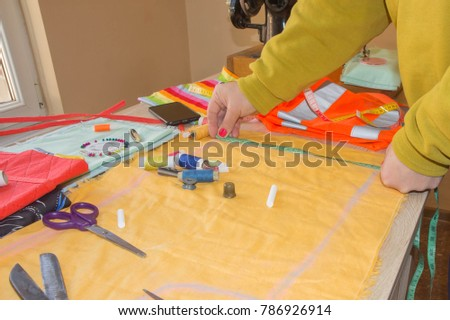 Fashion designer, Woman tailor posing at her workplace with cut fabric, free space on wooden work table. Garment industry, tailoring concept #786926914