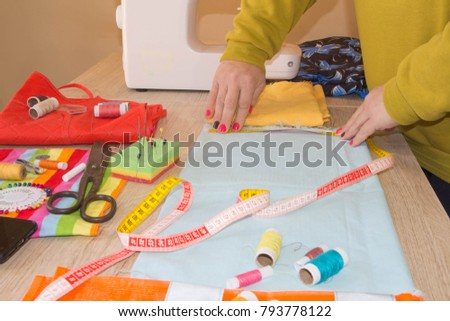 Fashion designer, Woman tailor posing at her workplace with cut fabric, free space on wooden work table. Garment industry, tailoring concept #793778122