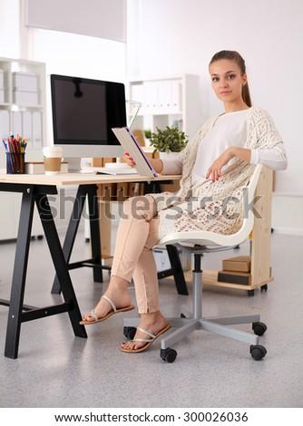 Fashion designers working in studio sitting on the desk