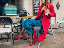 fashion details of accessories of stylish woman sitting in city street cafe in red coat, autumn style trend, drinking coffee, wearing blue silk dress, high heeled shoes, legs in black net stockings