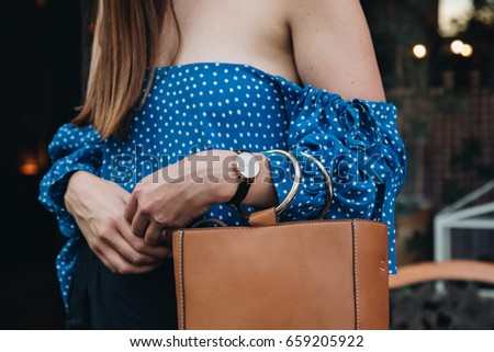 fashion details. woman wearing a blue polka dot off the shoulder top. holding a brown bag. wearing a black and white watch. ideal summer outfit accessories. european fashion blogger streetstyle. #659205922
