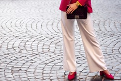 Fashion details: woman wearing white wide-leg trousers, pink blazer, wrist watch, pointed toe shoes, holding velvet violet quilted bag, posing in street of european city. Copy, empty space for text