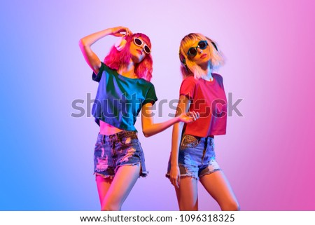 Fashion. Disco party woman have fun dance. Two DJ girl in colorful neon light enjoy music, friends. Party disco 80s 90s neon nightclub vibes. Pop art. Creative fashionable neon style