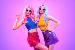 Fashion. Disco party woman have fun dance. Two DJ girl in colorful neon light, sisters. Beautiful model, stylish hair, 80s 90s neon nightclub fashionable style. Pop art. Creative neon light