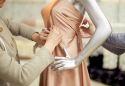 Fashion, dressmaking or tailoring concept. Professional team of tailors, dressmakers or designers working with new model applying linen fabrics beige cloth on mannequin or dummy in atelier