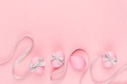 Fashion easter background - pink eggs with grey ribbon quaint stripes as border on pastel pink color.