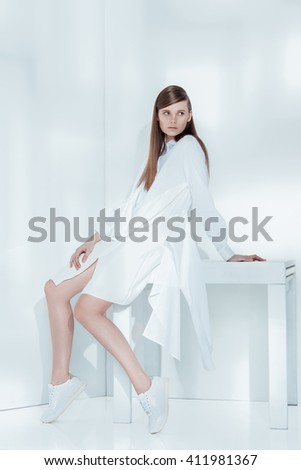 Fashion editorial shot in studio with white background. Beautiful model posing in total white clothes. - Shutterstock ID 411981367