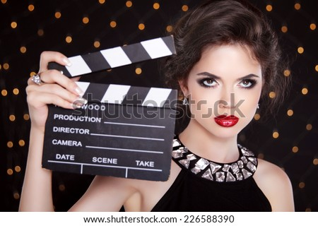 Fashion elegant woman with sexy red lips holding cinema clap. Super star model shot