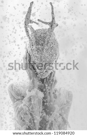 Fashion fantastic miracle model face in silver mask Christmas deer horns on white snow background