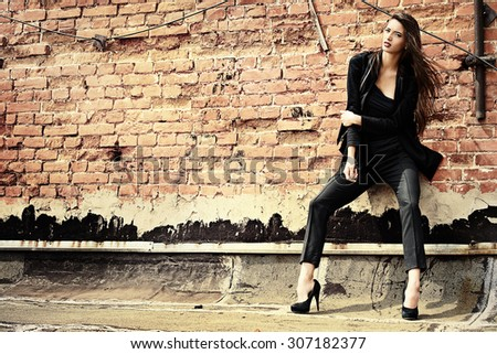 Fashion female model alluring outdoor by the brick wall. City style. Fashion photo.