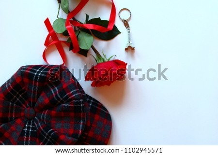 Fashion feminine blogger concept. Minimal set of woman accessories on white background. Still life of red objects: rose and women's kepi. Copy space for text. Isolated top view #1102945571