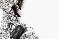 Fashion flat lay with white dress polka dot, shoes, black bag and accessories, monochrome concept, female look. Copy space, top view