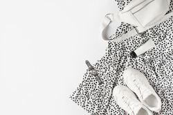 Fashion flat lay with white dress polka dot, sneakers, waist bag and accessories, monochrome concept, casual look. Copy space, top view,