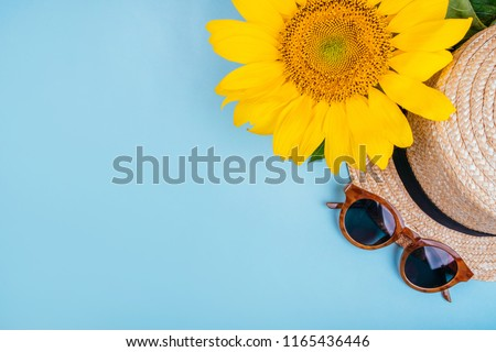Fashion flatlay with sunglasses, straw boater hat and bright big yellow sunflower on blue background. Flatlay style.
